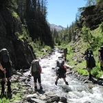 Crossing water with backpacks on in Wyoming