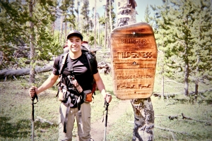Photo of Miles Shen beside a sign for Bridger Wilderness, located inside Bridger-Teton National Forest in Wyoming