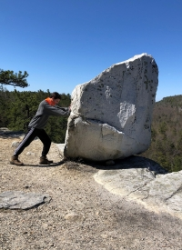 Eamon next to a large boulder on a hike in New York state.